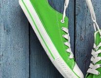 Espadrilles vert clair de textile accrochant sur la dentelle blanche Images libres de droits
