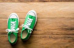 Espadrilles vertes sur les planchers en bois - mode de vie Photo stock