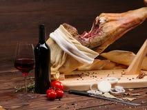 Espagnol Jamon sur le jamonera en bois de table avec les tomates, le verre et la bouteille de vin rouge Photographie stock