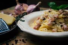 Espaguete Carbonara Carbonara do alla da massa com um molho de creme, um bacon e uma pimenta em uma placa branca fotografia de stock royalty free