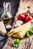 espaguete Queijo parmesão e cogumelos do azeite da manjericão dos tomates dos espaguetes na placa muito velha do carvalho imagem de stock royalty free