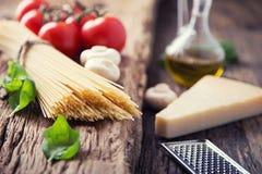 espaguete Queijo parmesão e cogumelos do azeite da manjericão dos tomates dos espaguetes na placa muito velha do carvalho imagem de stock