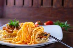 Espaguetes com molho no prato na tabela de madeira imagem de stock royalty free