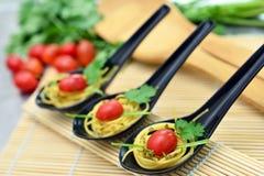 Espaguetes com tomates e salsa de cereja em colheres Fotografia de Stock Royalty Free