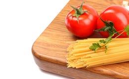 Espaguetes crus, alho e tomates Fotos de Stock Royalty Free