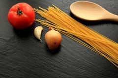 Espaguetes crus com tomate, alho, cebola e a pá de pedreiro de madeira Foto de Stock Royalty Free