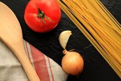 Espaguetes crus com tomate, alho, cebola e a pá de pedreiro de madeira com toalha de cozinha Fotografia de Stock