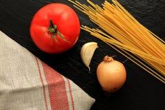 Espaguetes crus com tomate, alho, cebola e toalha de cozinha Fotografia de Stock