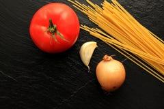 Espaguetes crus com tomate, alho e cebola Fotos de Stock Royalty Free