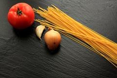Espaguetes crus com tomate, alho e cebola Fotografia de Stock
