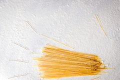 Espaguetes crus da massa no fundo branco floured Entregue feixes tirados na tabela, estilo simples do sol Foto de Stock