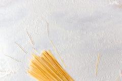 Espaguetes crus da massa no fundo branco floured Entregue feixes tirados na tabela, estilo simples do sol Fotografia de Stock