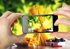 Espaguetes da foto com seu smartphone Imagem de Stock Royalty Free