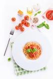 Espaguetes da massa do tomate com tomates frescos, manjericão, as ervas italianas e o azeite em uma bacia branca em um fundo de m Foto de Stock