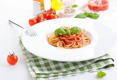 Espaguetes da massa do tomate com tomates frescos, manjericão, as ervas italianas e o azeite em uma bacia branca em um fundo de m Imagens de Stock Royalty Free