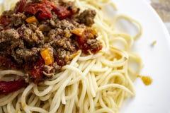 Espaguetes deliciosos bolonhês na placa branca foto de stock
