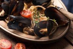 Espaguetes deliciosos e mexilhões italianos tradicionais cozinhados no molho foto de stock