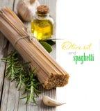 Espaguetes do trigo, alho, óleo do oilve e ervas inteiros Imagens de Stock