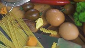 Espaguetes e macarrão italianos com ovos frescos e o vegetal cru na tabela de madeira Ingrediente de alimento italiano para cozin video estoque