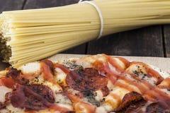 Espaguetes frescos e uma pizza de pepperoni Fotografia de Stock Royalty Free