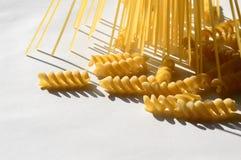 Espaguetes, fusilli na luz do sol na tabela branca imagens de stock