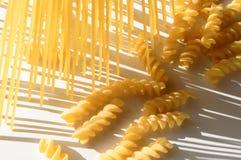 Espaguetes, fusilli na luz do sol na tabela branca fotografia de stock royalty free