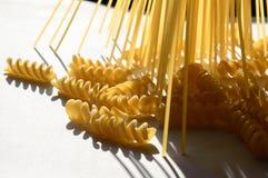 Espaguetes, fusilli na luz do sol na tabela branca fotos de stock
