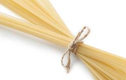 Espaguetes italianos crus amarrados com corda Isolado em branco, macro Fotografia de Stock