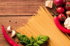 Espaguetes italianos da massa com legumes frescos e especiarias - vista superior no fundo de madeira fotos de stock royalty free