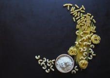 Espaguetes italianos da massa, tagliatelle, fusilli, cavatappi no fundo preto Massa na forma de um crescente Foto de Stock