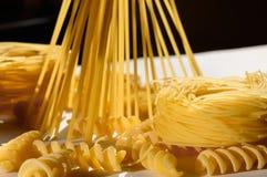 Espaguetes, massa do ninho, fusilli na luz do sol na tabela branca Foto de Stock Royalty Free
