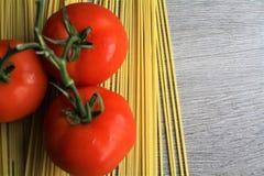 Espaguetes & tomates na tabela de madeira imagem de stock royalty free