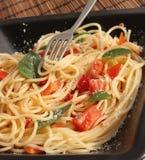 Espagueti con los tomates y la albahaca Imágenes de archivo libres de regalías