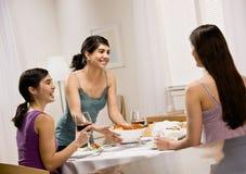 Espagueti de la porción de la mujer a los amigos Foto de archivo libre de regalías