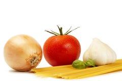 Espagueti sin procesar con el tomate, la albahaca, el ajo y la cebolla Imagenes de archivo