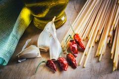 Espaguetis, aceite de oliva, ajo y chiles Foto de archivo libre de regalías