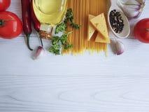 Espaguetis, aceite de oliva, queso, ajo, tomates en un marco de madera Fotografía de archivo libre de regalías