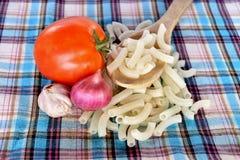 Espaguetis, ajo de los macarrones, tomate y chalotes en tela Foto de archivo libre de regalías