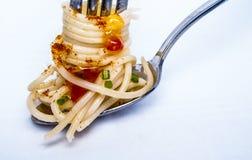 Espaguetis amarillos en una cuchara y una bifurcación imagenes de archivo
