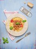 Espaguetis boloñés con la bifurcación y rallador viejo del parmesano en fondo de madera azul imagen de archivo