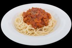 Espaguetis boloñés con la salsa de tomate del cerdo o de la carne en una placa aislada en el fondo negro con la trayectoria de re fotografía de archivo