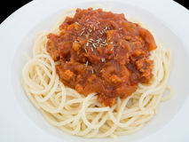 Espaguetis boloñés en una placa en el fondo negro imagen de archivo