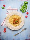 Espaguetis boloñés con los tomates y albahaca en fondo de madera azul Fotografía de archivo