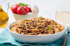Espaguetis boloñés con queso y albahaca en los ingredientes de un italiano de la placa Fotos de archivo