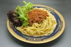 Espaguetis boloñés, salsa de tomate de la carne con lechuga Foto de archivo libre de regalías