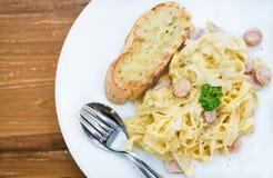Espaguetis Carbonara con el jamón y el queso en el escritorio Fotos de archivo libres de regalías