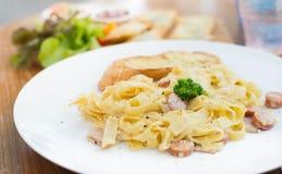 Espaguetis Carbonara con el jamón y el queso en el escritorio imagen de archivo libre de regalías