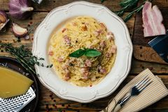 Espaguetis Carbonara Carbonara del alla de las pastas con una salsa cremosa, un tocino y una pimienta en una placa blanca imagenes de archivo