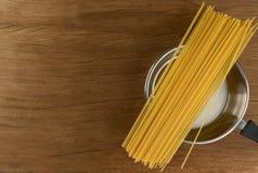 Espaguetis con artículos de cocina en fondo de madera de la tabla Fotos de archivo