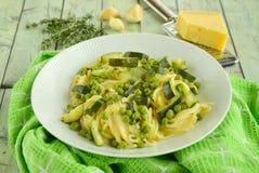 Espaguetis con el calabacín y los guisantes Foto de archivo